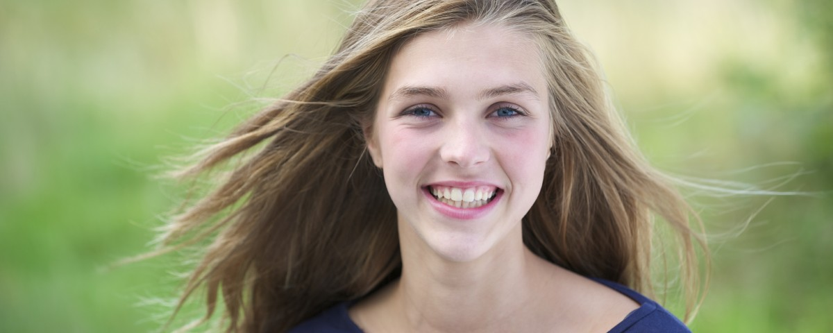 Portrait of a pretty teenage girl outside smiling